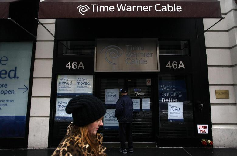 A woman walks past the old Time Warner Cable headquarters as a man tries to enter the building in New York February 13, 2014. REUTERS/Joshua Lott