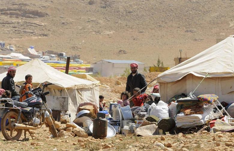 Refugees who fled the violence from the Syrian town of Flita, near Yabroud, stand outside their tents at the border town of Arsal, in the eastern Bekaa Valley March 20, 2014 file photo. REUTERS/Hassan Abdallah