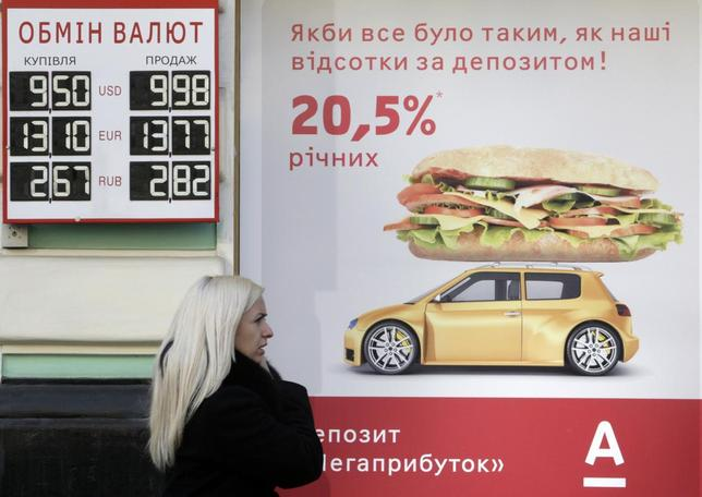 A woman speaks on the phone near a board with currency exchange rates in Kiev, February 26, 2014. REUTERS/Konstantin Chernichkin