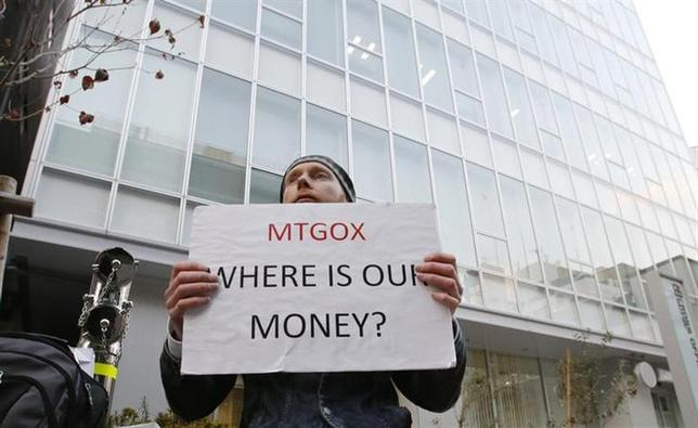 Kolin Burges, a self-styled cryptocurrency trader and former software engineer who came from London, holds a placard to protest against Mt. Gox, in front of the building where the digital marketplace operator is housed in Tokyo February 25, 2014. REUTERS/Toru Hanai/Files