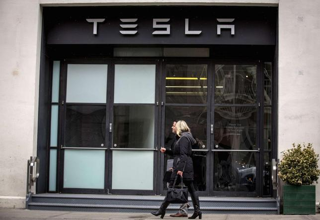 People pass by the Tesla New York City store is seen in the Chelsea neighborhood of New York March 19, 2014. REUTERS/Brendan McDermid