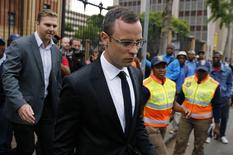 Oscar Pistorius leaves court after his trial for the murder of his girlfriend, Reeva Steenkamp, was postponed at the North Gauteng High Court in Pretoria March 28, 2014. REUTERS/Siphiwe Sibeko