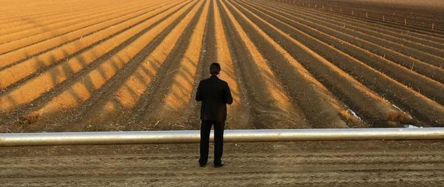 A Secret Service Agent keeps watch as U.S. President Barack Obama tours a drought affected farm field in Los Banos, California February 14, 2014. REUTERS/Kevin Lamarque