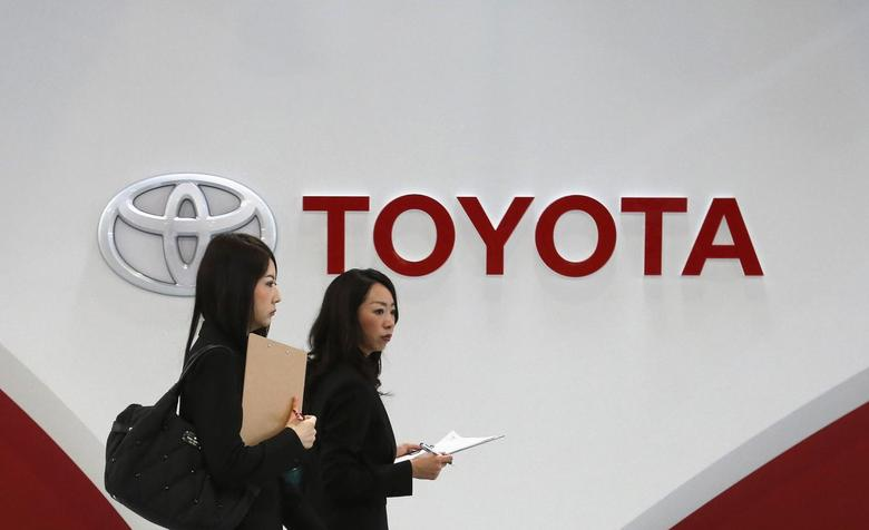Women walk in front of Toyota Motor's logo at the company's showroom in Tokyo March 12, 2014. REUTERS/Toru Hanai