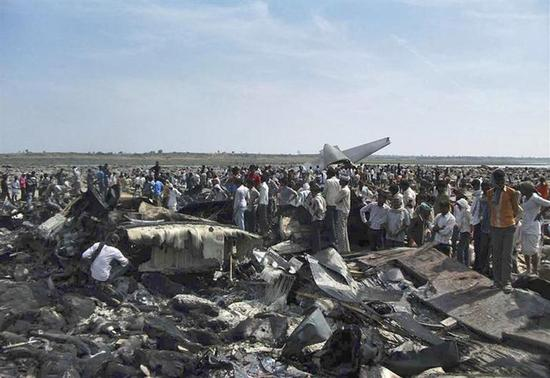 Onlookers stand next to the debris of a crashed U.S.-made C-130J Hercules aircraft of Indian Air Force (IAF) in the central Indian state of Madhya Pradesh March 28, 2014. REUTERS/Stringer