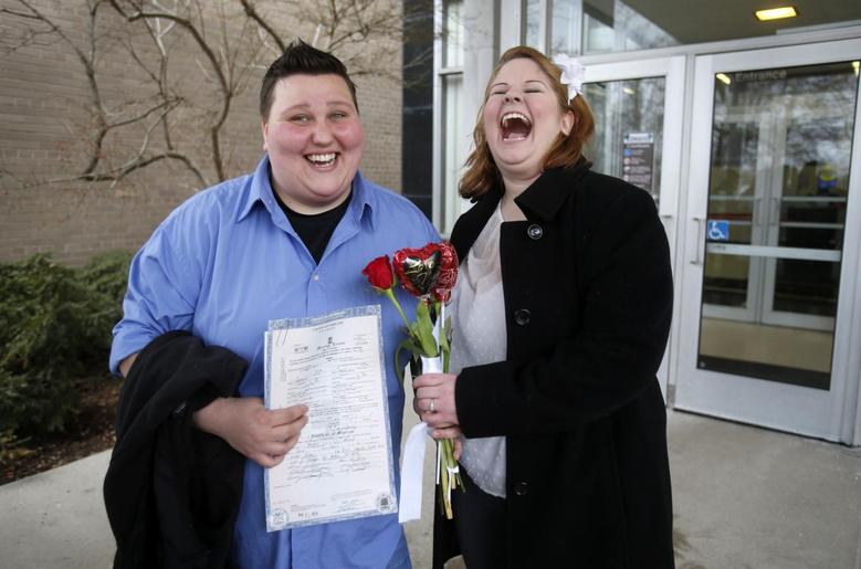 Newly married Sarah Brown (L) and Dolly Vanfossan hold their marriage license outside after being married at the Oakland County Courthouse, after a Michigan federal judge ruled a ban on same-sex marriage violates the U.S. Constitution and must be overturned in Pontiac, Michigan March 22, 2014. REUTERS/Rebecca Cook