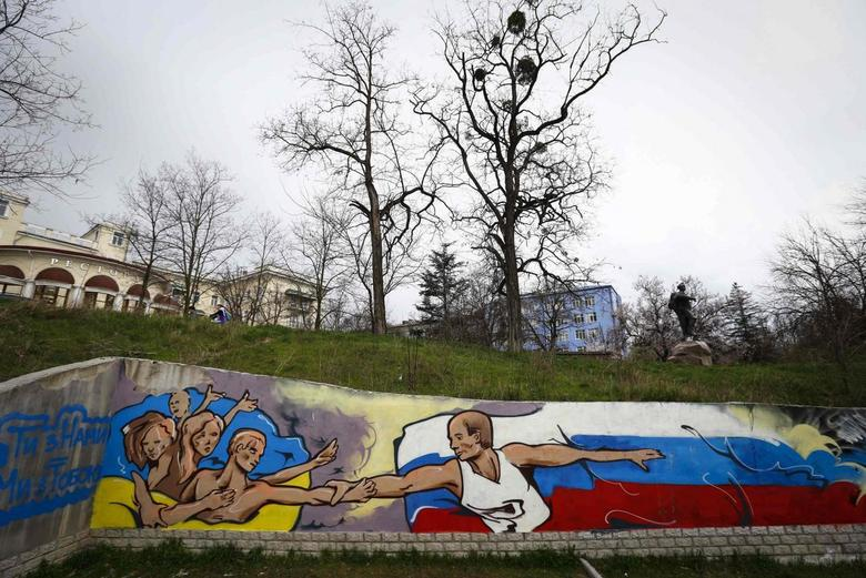 Graffiti depicting Russian President Vladimir Putin (R) extending a hand to the Ukrainian people is seen on a wall in the Crimean city of Simferopol March 28, 2014. REUTERS/Shamil Zhumatov