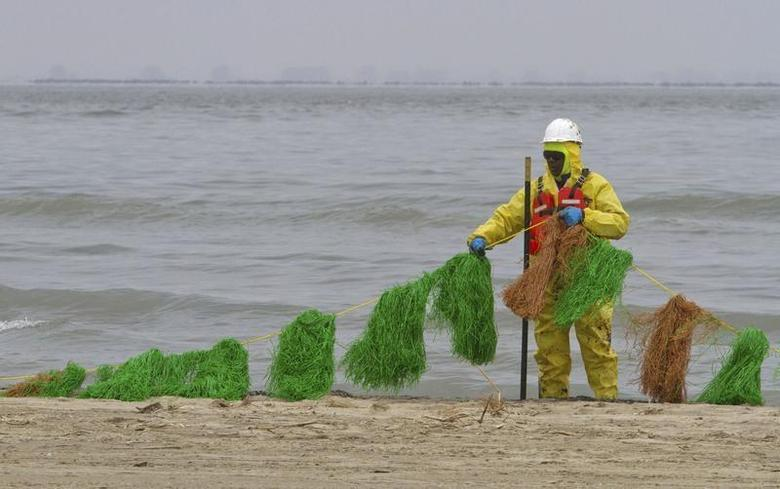 A worker places oil absorbent snares on the beach on the east end of Galveston Island March 24, 2014. REUTERS/Richard Carson