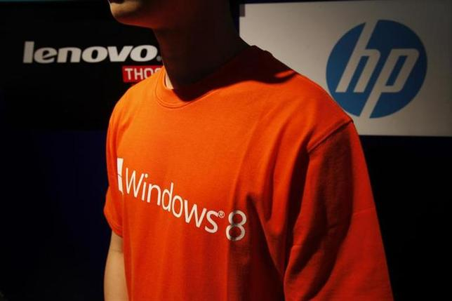 An attendant stands in front of logos of two top computer brands, Lenovo and HP, during the launch of Microsoft Windows 8 operating system in Hong Kong October 26, 2012. REUTERS/Bobby Yip