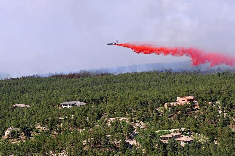 An aircraft releases a fire-retardant solution to help stop the spreading of the burning fires at Black Forest, Colorado, in this handout photo taken June 12, 2013. REUTERS/US Army