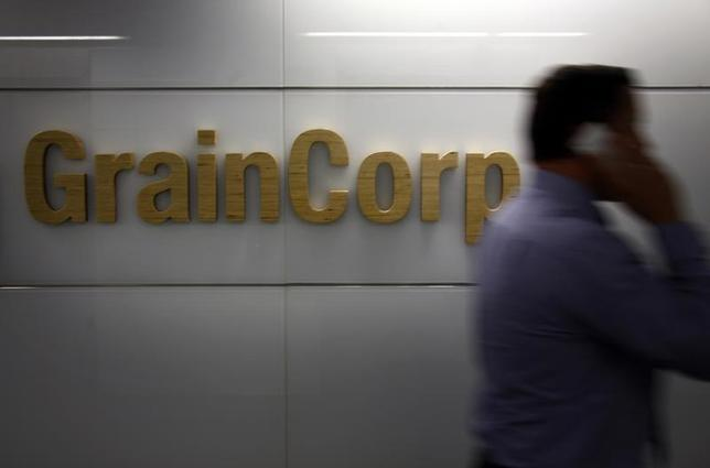 A worker at the Sydney headquarters for GrainCorp walks past a company sign November 29, 2013. REUTERS/David Gray