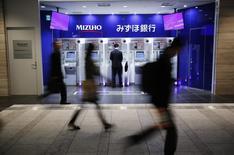 A man uses an ATM machine of Mizuho Bank as pedestrians walk past at a train station in Tokyo November 13, 2013. REUTERS/Yuya Shino