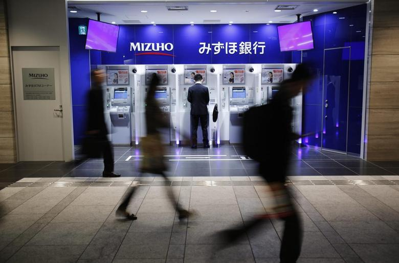 A man uses an ATM machine of Mizuho Bank as pedestrians walk past at a train station in Tokyo November 13, 2013. REUTERS/Yuya Shino