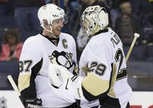 Mar 28, 2014; Columbus, OH, USA; Pittsburgh Penguins center Sidney Crosby (87) celebrates with goalie Marc-Andre Fleury (29) after defeating the Columbus Blue Jackets 2-1 at Nationwide Arena. Mandatory Credit: Greg Bartram-USA TODAY Sports