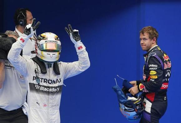 Mercedes Formula One driver Lewis Hamilton of Britain (L) celebrates next to Red Bull Formula One driver Sebastian Vettel of Germany after the qualifying session for the Malaysian F1 Grand Prix at Sepang International Circuit outside Kuala Lumpur, March 29, 2014. REUTERS/Samsul Said