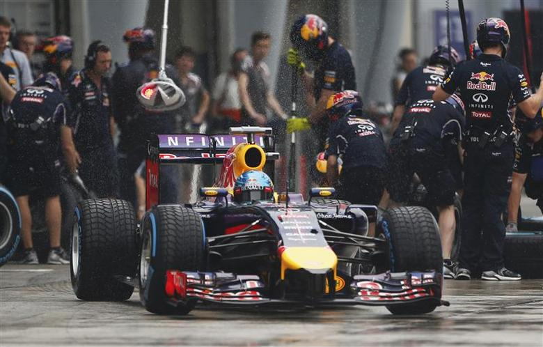 Red Bull Formula One driver Sebastian Vettel of Germany leaves his team garage during the qualifying session for the Malaysian F1 Grand Prix at Sepang International Circuit outside Kuala Lumpur, March 29, 2014. REUTERS/Peter Lim/Pool