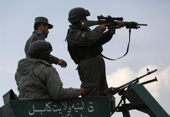 Afghan policemen take their positions atop a military vehicle near an election commission office during an attack by gunmen in Kabul March 29, 2014. REUTERS/Mohammad Ismail