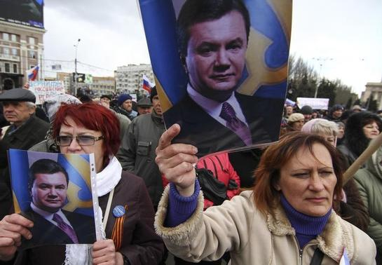 Pro-Russian activists hold pictures of ousted Ukrainian President Victor Yanukovich during a protest in central Donetsk March 29, 2014. REUTERS/Stringer