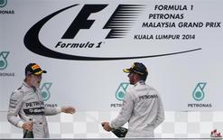 Mercedes Formula One driver Lewis Hamilton of Britain sprays champagne at team mate second-placed Nico Rosberg of Germany after winning the Malaysian F1 Grand Prix at Sepang International Circuit outside Kuala Lumpur, March 30, 2014. REUTERS/Edgar Su