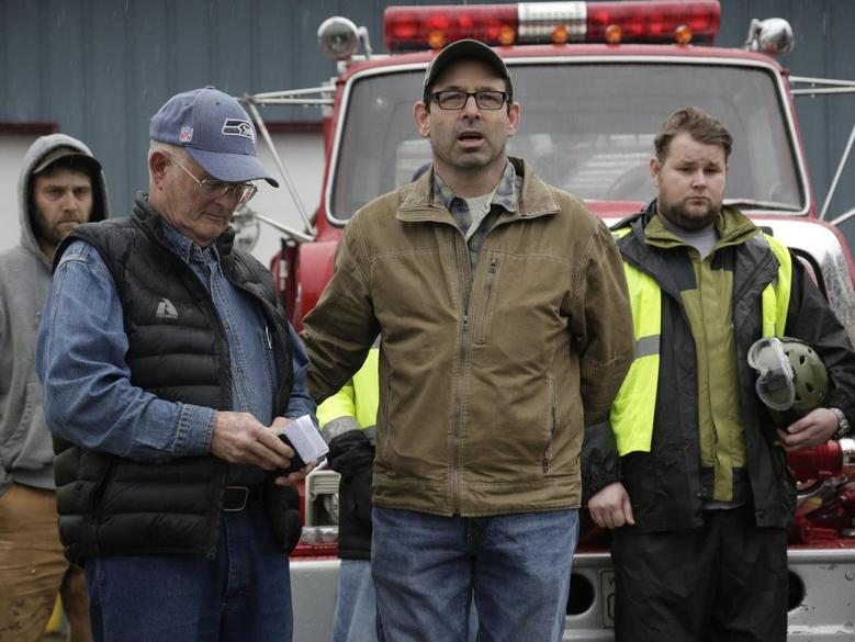 Darrington Mayor Dan Rankin (2nd R) and Pastor Mike De Luca (2nd L) lead workers and community members in prayer and a moment of silence marking the one-week anniversary of the Oso landslide at the fire station in Darrington, Washington March 29, 2014. REUTERS/Jason Redmond
