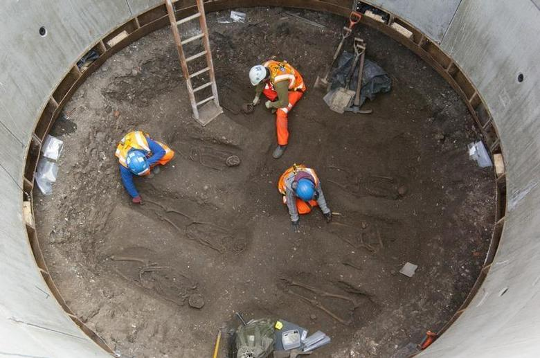 Archaeologists work on unearthed skeletons in the Farringdon area of London in this undated handout photograph released March 15, 2013. REUTERS/Crossrail/Handout