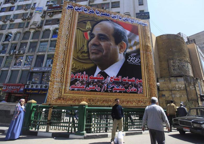 People stand under a huge banner of Egypt's former army chief Abdel Fattah al-Sisi in downtown Cairo March 27, 2014. REUTERS/Amr Abdallah Dalsh