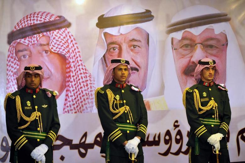 Saudi royal guards stand on duty in front of portraits of King Abdullah bin Abdulaziz (R), Crown Prince Salman bin Abdulaziz (C) and second deputy Prime Minister Muqrin bin Abdulaziz during the traditional Saudi dance known as ''Arda'' at the Janadriya culture festival at Der'iya in Riyadh, February 18, 2014. REUTERS/Fayez Nureldine/Pool