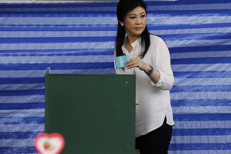 Thai Prime Minister Yingluck Shinawatra prepares to cast a ballot at a polling station in Bangkok March 30, 2014. REUTERS/Chaiwat Subprasom