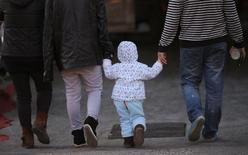A girl holds the hands of her parents as they walk on a street in Beijing, November 18, 2013. REUTERS/Kim Kyung-Hoon
