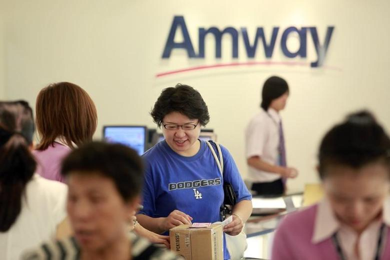 A woman buys Amway products inside the company's sales showroom in Taipei July 31, 2009. REUTERS/Nicky Loh
