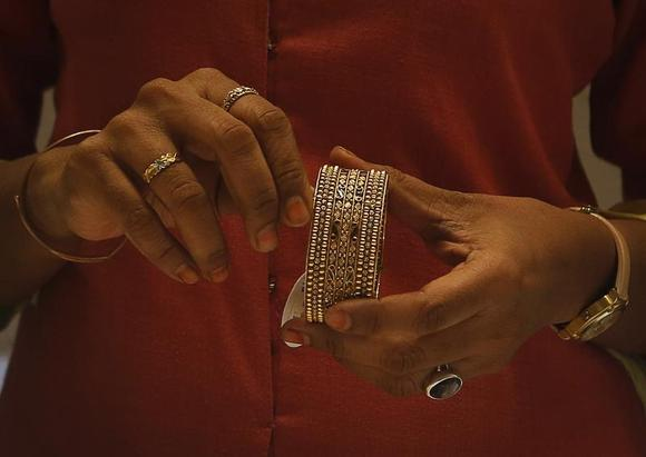 An employee shows a gold bangle to a customer inside a jewellery showroom in Mumbai August 30, 2013. REUTERS/Danish Siddiqui/Files