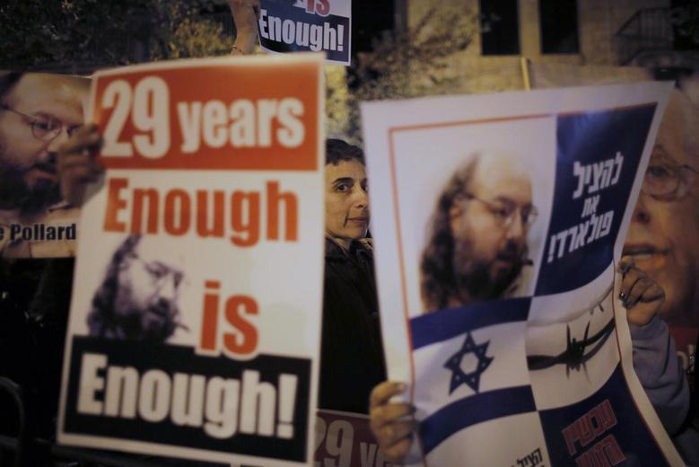 Israelis hold placards depicting Jonathan Pollard during a protest calling for his release from a U.S. prison, outside U.S. Secretary of State John Kerry's hotel in Jerusalem January 2, 2014. The placard (R) in Hebrew reads ''To save Pollard!''. REUTERS/Ammar Awad