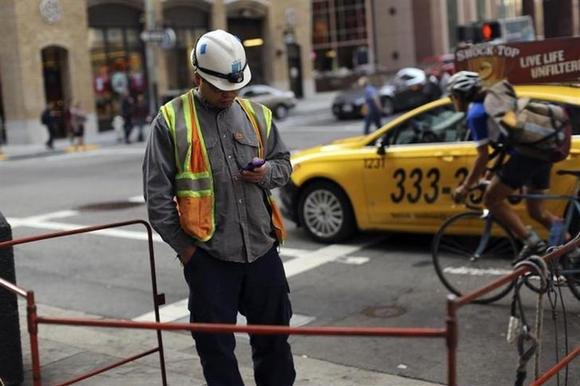 A worker looks at his smartphone in the financial district in San Francisco, California November 6, 2013. REUTERS/Robert Galbraith/Files