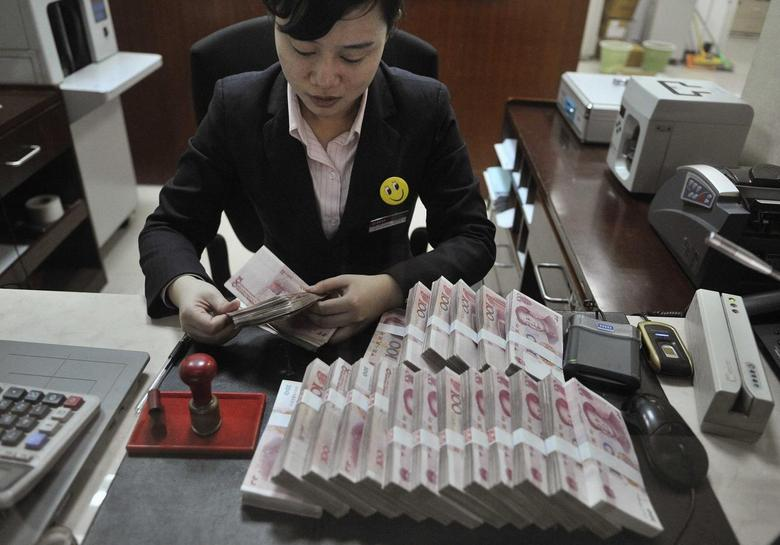 A clerk counts 100 Chinese yuan banknotes at a branch of China Merchants Bank in Hefei, Anhui province March 17, 2014. REUTERS/Stringer