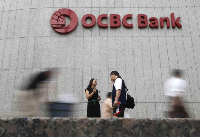 Office workers pass a logo of Overseas-Chinese Banking Corp Ltd (OCBC) at the company's headquarters in Singapore February 14, 2014. REUTERS/Edgar Su