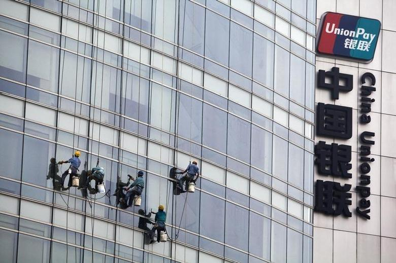 Workers clean windows next to the logo of China Unionpay at the company's headquarters in Shanghai, in this picture taken September 20, 2008. REUTERS/Stringer