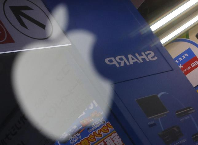 The logo of Sharp Corp is seen reflected on Apple Inc's MacBook Pro at an electronics store in Tokyo in this January 15, 2013 file photo. REUTERS/Toru Hanai/Files