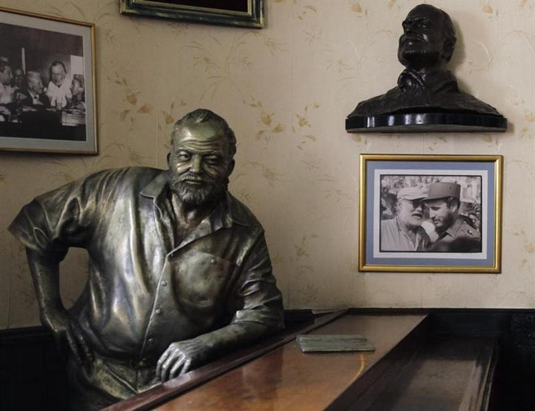 A life-size bronze statue of U.S. writer Ernest Hemingway at his regular spot at The Floridita bar stands beside a picture of former Cuban leader Fidel Castro and the writer taken when they met at a fishing competition in Havana on May 15, 1960, in Havana, July 1, 2010. REUTERS/Desmond Boylan