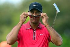 Mar 9, 2014; Miami, FL, USA; Tiger Woods puts on his sunglasses on the 3rd hole green during the final round of the WGC - Cadillac Championship golf tournament at TPC Blue Monster at Trump National Doral. Mandatory Credit: Andrew Weber-USA TODAY Sports