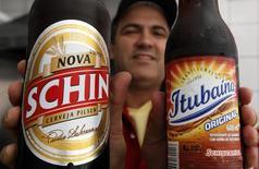 Um garçom mostra uma garrafa de cerveja e uma de refrigerante, ambos fabricados pela Schincariol. O governo elevou os impostos das cervejas, refrescos, isotônicos e energéticos, num movimento que vai gerar receitas extras de 200 milhões de reais, segundo informou o Ministério da Fazenda por meio de nota nesta terça-feira. 02/08/2011 REUTERS/Nacho Doce