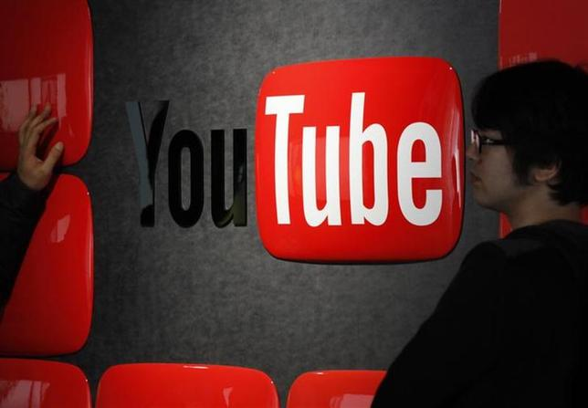 Visitors stand in front of a logo of YouTube at the YouTube Space Tokyo, operated by Google, in Tokyo February 14, 2013. REUTERS/Shohei Miyano/Files