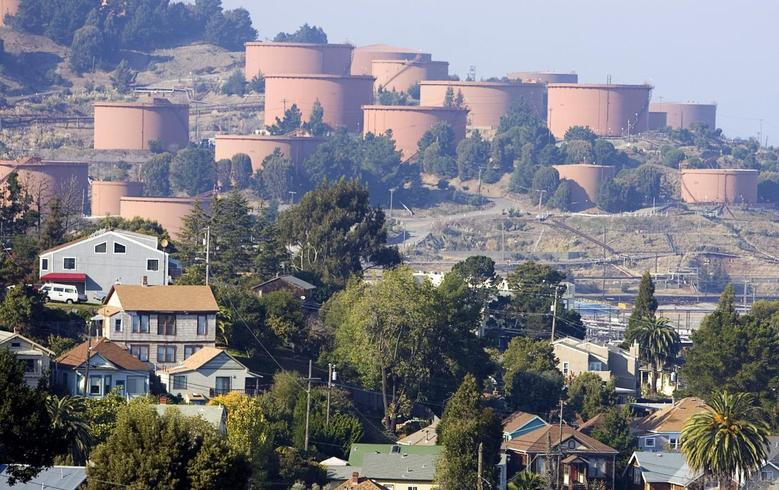 Homes sit below Chevron storage tanks on a hillside in Richmond, California, in this November 6, 2007 file photo. REUTERS/Kimberly White/Files