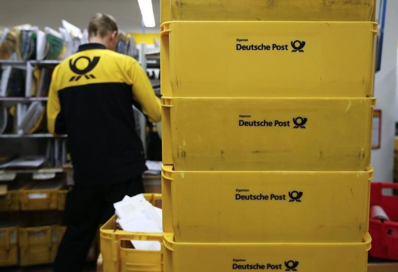 Transport boxes are pictured next to a postman of the German postal and logistics group Deutsche Post who is sorting mail at a sorting office in Berlin's Mitte district, December 4, 2013. REUTERS/Fabrizio Bensch