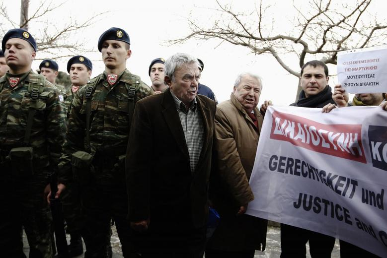 Members of the ''National Committee to Claim German Debt'' stage a protest during the visit of German President Joachim Gauck at the monument for the victims of a World War Two massacre in the village of Ligiades, northwestern Greece March 7, 2014. REUTERS/Alkis Konstantinidis