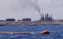 Порт и НПЗ в ливийском городе Эз-Завия 22 августа 2013 года. Цены на нефть Brent держатся выше $105 за баррель и недалеко от пятимесячного минимума накануне официального отчета о запасах нефти в США. REUTERS/Ismail Zitouny