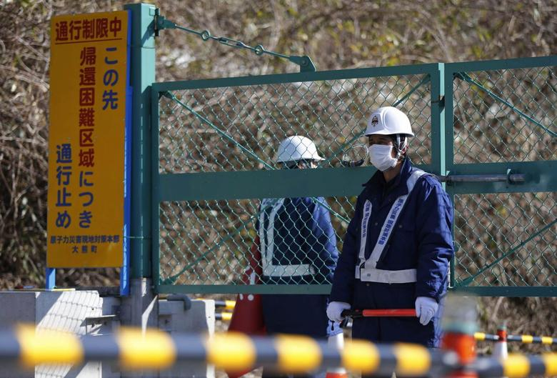 Security personnel stand guard near a steel gate that marks the border between Tamura and Okuma town in Okuma town, Fukushima prefecture April 1, 2014. The signboard (L) reads: ''No Entry Due To The Area Off-Limits for Residence''. REUTERS/Issei Kato