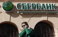 Мужчина проходит мимо отделения Сбербанка в Санкт-Петербурге 27 марта 2014 года. Крупнейший госбанк РФ Сбербанк с 1 апреля прекратил выдачу валютных кредитов населению с целью обезопасить свой кредитный портфель от волатильности курсов. REUTERS/Alexander Demianchuk
