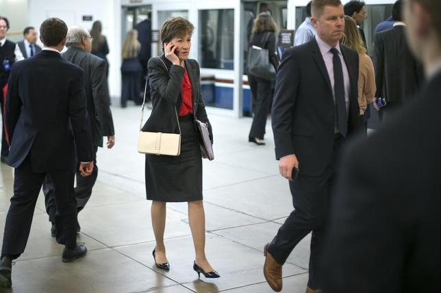U.S. Senator Susan Collins (R-ME) (C) talks on a mobile phone as she arrives for the weekly Republican caucus luncheon at the U.S. Capitol in Washington, February 4, 2014. REUTERS/Jonathan Ernst