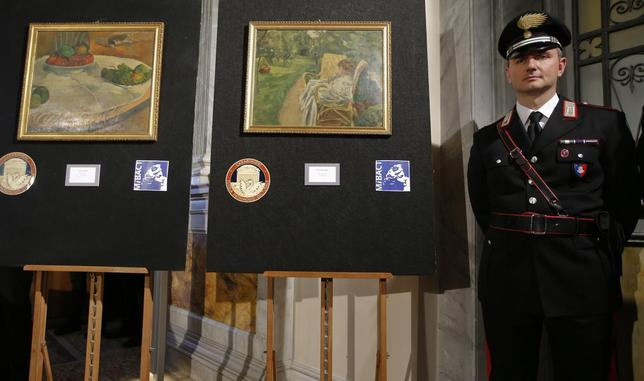 A Carabinieri police officer stands in front of two recovered paintings by Paul Gauguin and Pierre Bonnard during a news conference in Rome, April 2, 2014. A painting by French post-Impressionist artist Gauguin that was stolen in Britain in 1970 has turned up hanging in the kitchen of a retired factory worker in Sicily, Italian police said on Wednesday. REUTERS/Tony Gentile