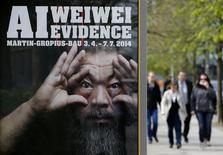 People walk beside an advertising poster for the exhibition 'Evidence' by Chinese artist Ai Weiwei at the Martin-Gropius Bau in Berlin, April 2, 2014. REUTERS/Fabrizio Bensch